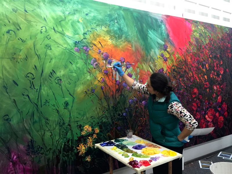 Erin Hanson painting a mural-sized oil painting landscape in her studio, in Los Angeles